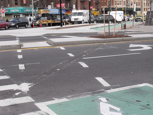 Cyclists can wait to cross Amsterdam Avenue in a bike box, before they enter a parking protected contra-flow lane on the other side. A pedestrian refuge island also shortens crossing distances and calms traffic. Photo: BicyclesOnly via Flickr.