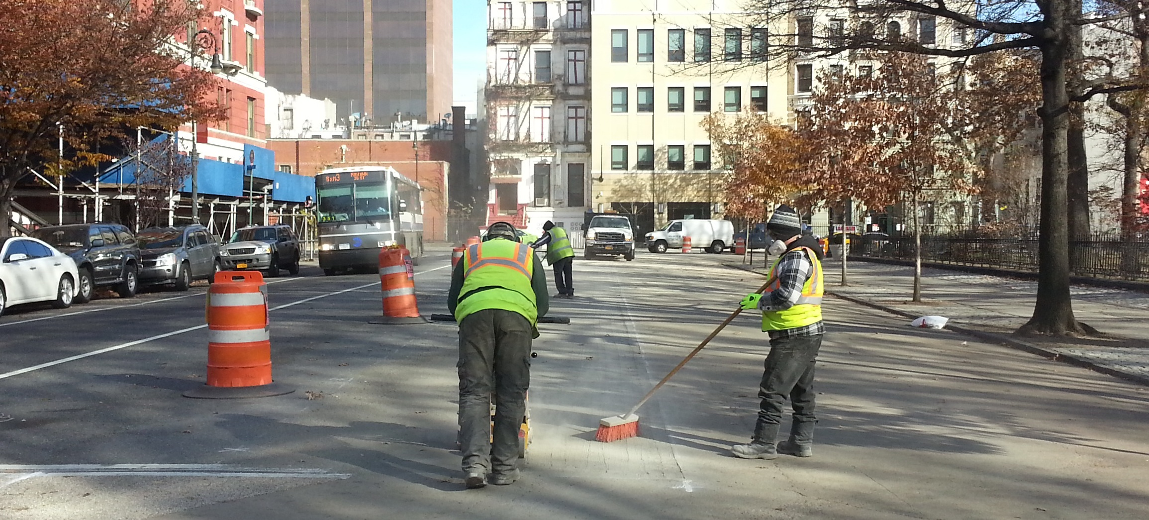 DOT crews at work yesterday morning, erasing part of the pedestrian space on Mount Morris Park West. Photo: Stephen Miller