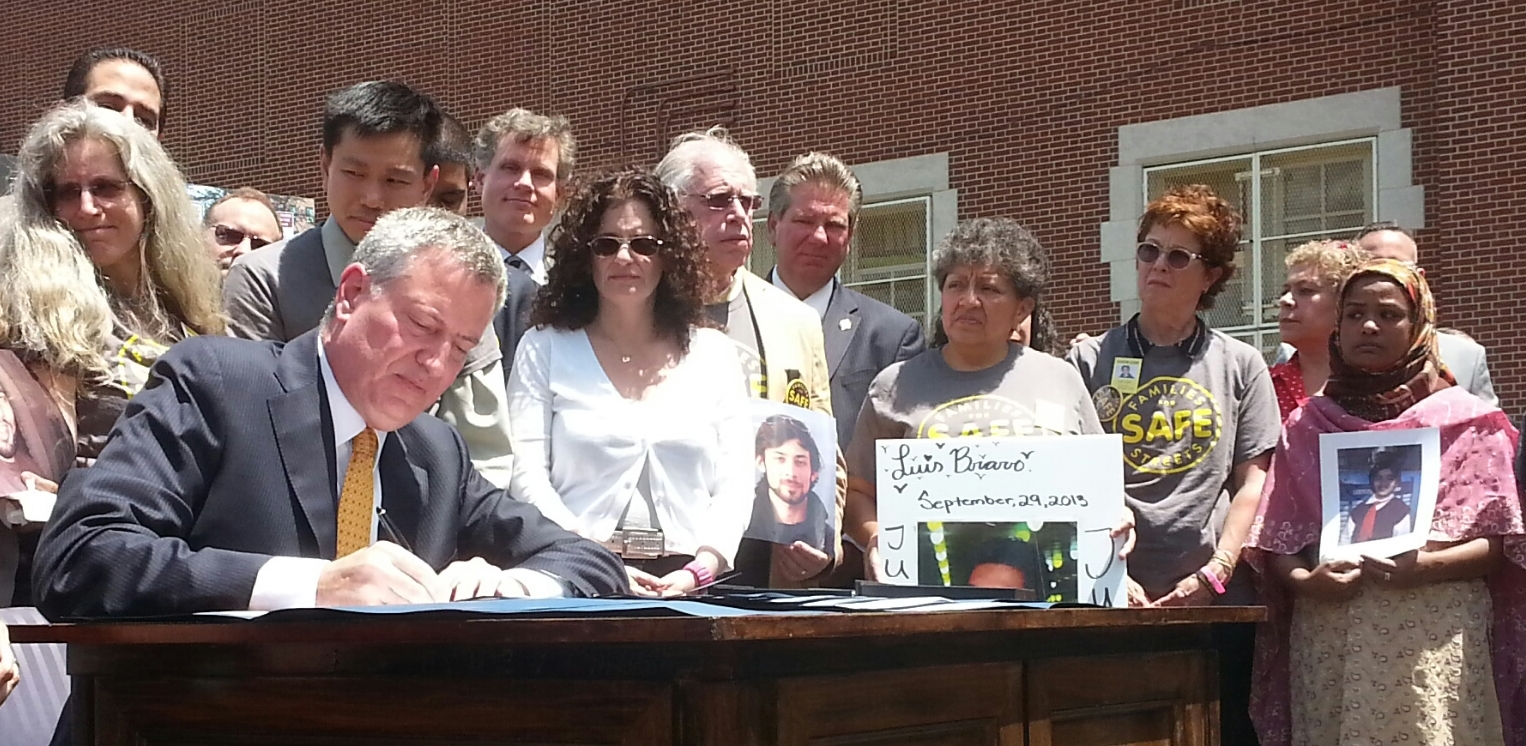Mayor de Blasio signs 11 traffic safety bills this morning at PS 152 in Queens, surrounded by families of traffic violence victims. Photo: Stephen Miller