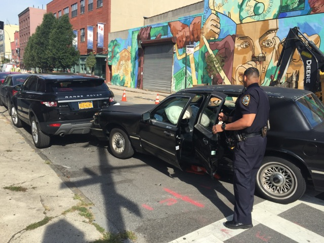An officer from the 78th Precinct inspects the vehicle on Degraw Street after its driver fled yesterday morning. Photo: Mike Donohue