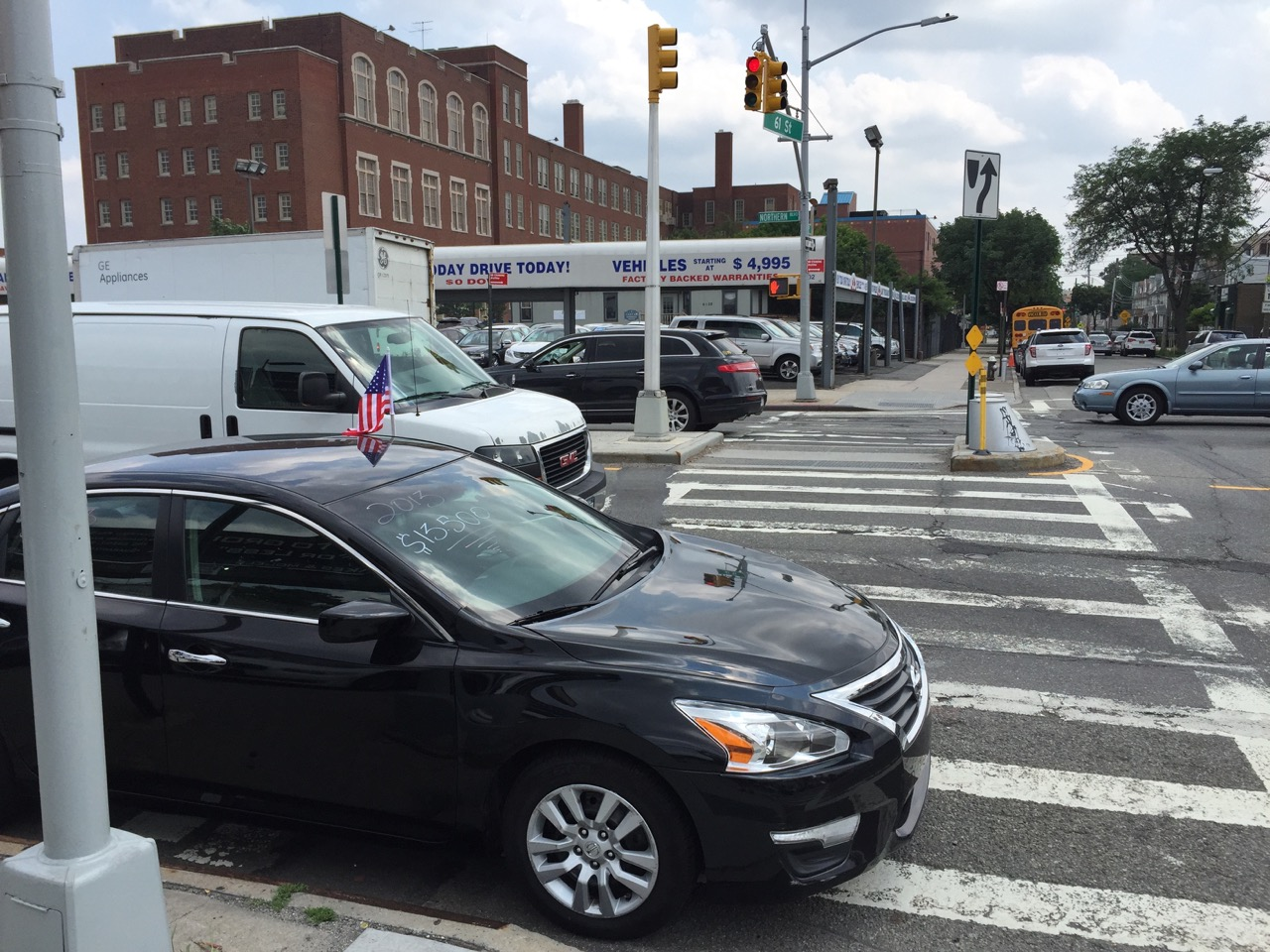 The crosswalk where 8-year-old Noshat Nahian was killed is blocked by a car dealership using it as a display space for its latest models. Photo: Clarence Eckerson Jr.