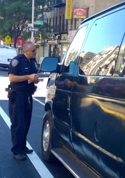 A 34th Precinct officer cites a driver blocking a bike lane on Sherman Avenue in Inwood. Photo: 34th Precinct/Facebook