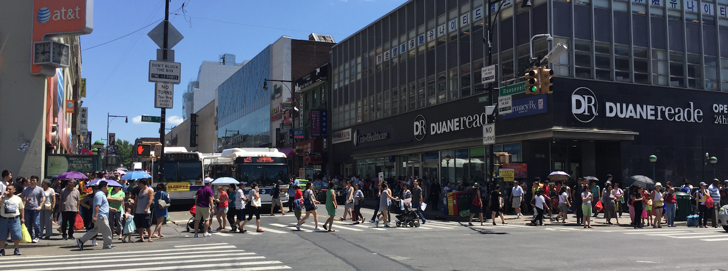 Pedestrians crossing Roosevelt Avenue at Main Street, the location of the Flushing-Main Street subway station, at around noon today. Photo: David Meyer