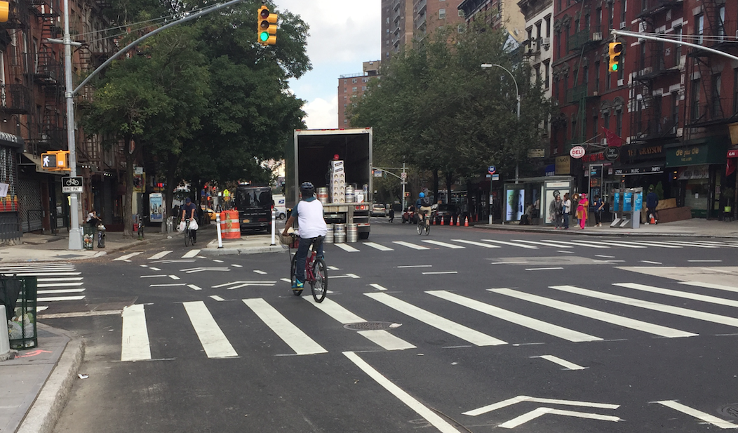 Cyclists entering the First Avenue protected bike lane at East First Street. Photo: David Meyer